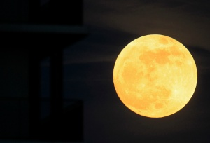 The moon rises near an apartment block in Bucharest