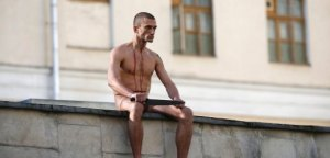 "Artist Pyotr Pavlensky sits on a wall after he cut off a part of his earlobe during his protest action titled ""Segregation"" in Moscow"